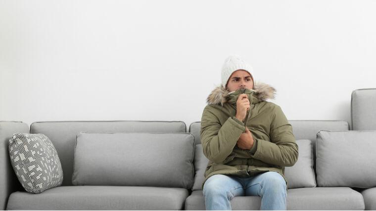 部屋の中で凍える男性