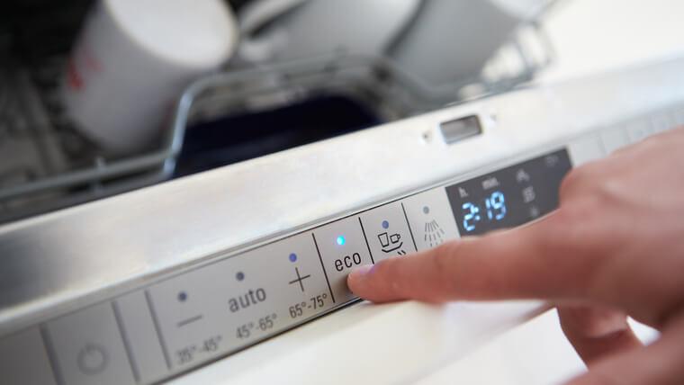 食器洗い機にエコノミーサイクルを設定する男性