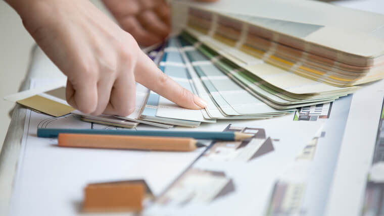 色見本帳で新築の外壁の色をチェックする女性